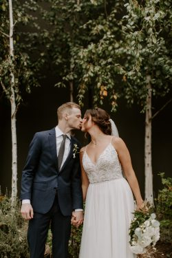 Groom Kissing Real Bride in Forest Wearing Boho A-line Wedding Gown Called Charlene by Maggie Sottero