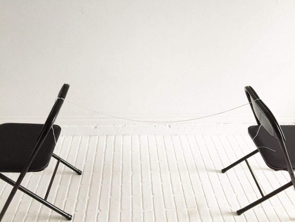 two black chairs holding up a piece of twine
