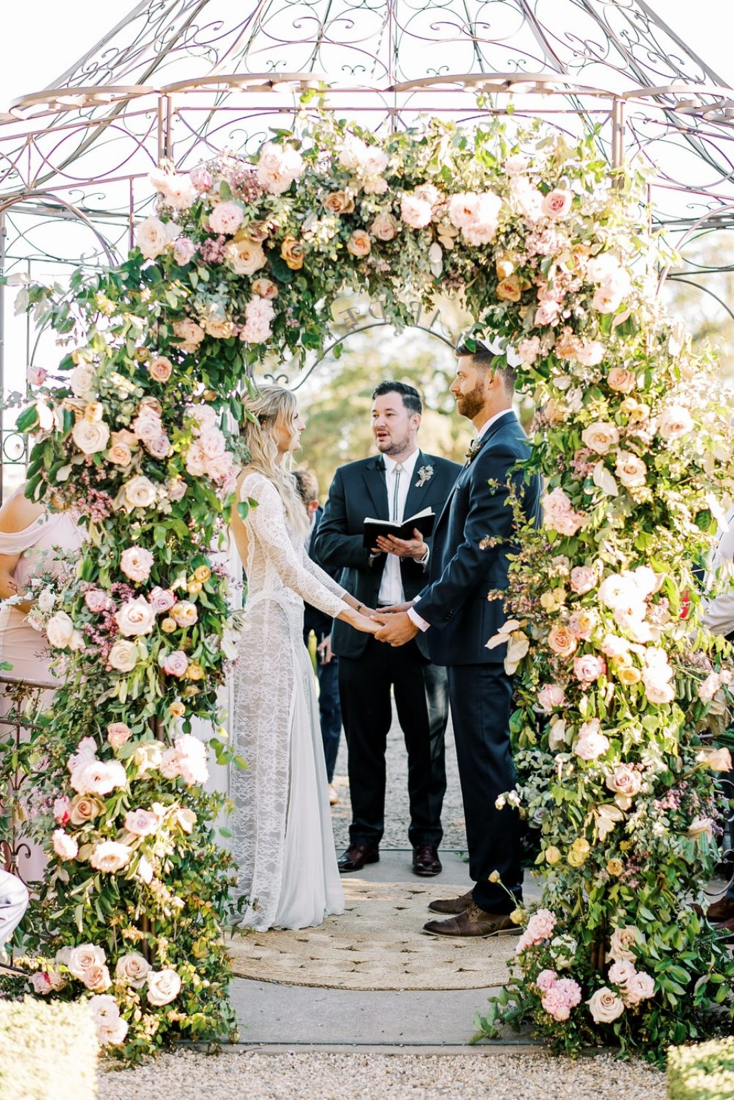 bride and groom under the floral arbor