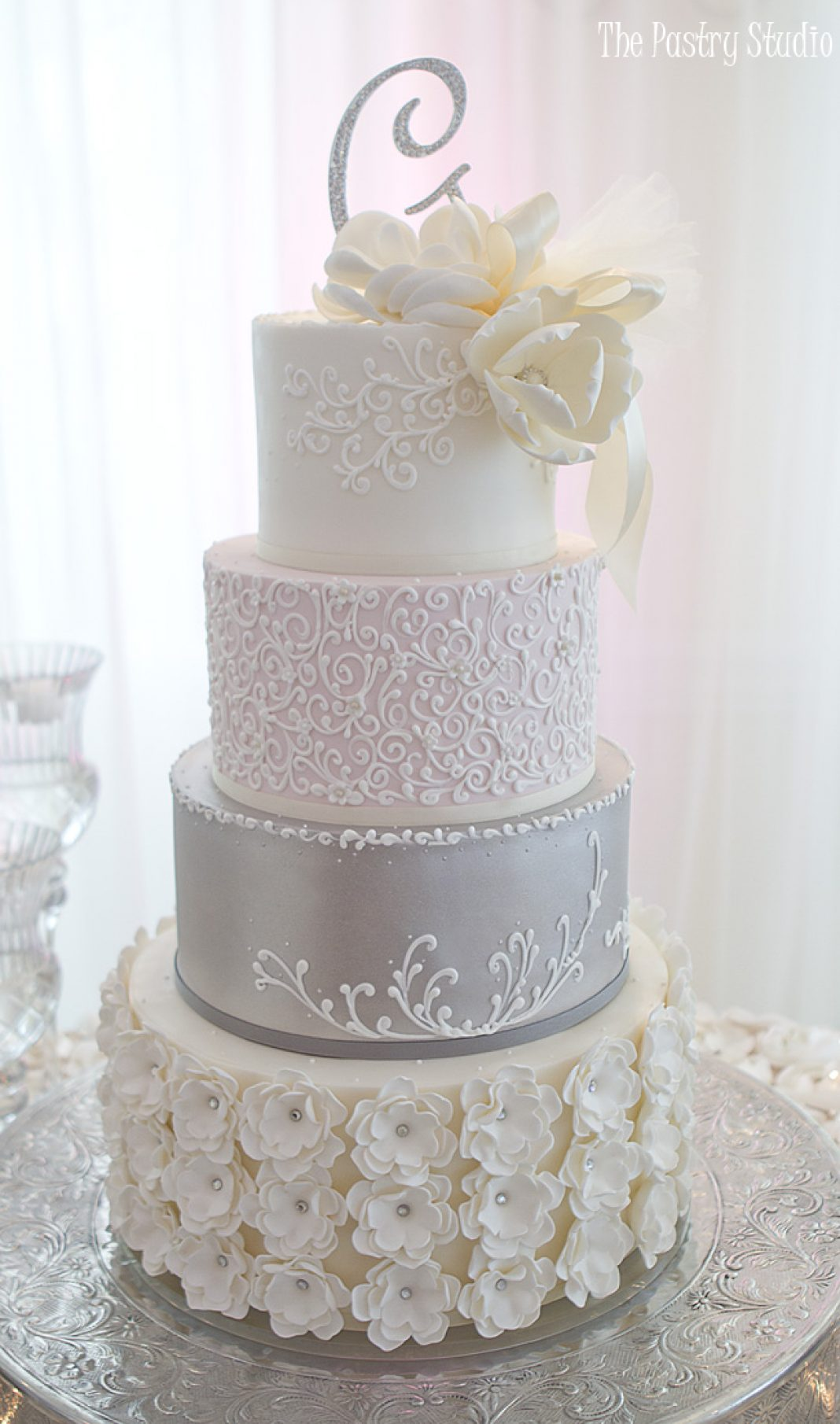 The Pastry Studio creates the most creative and delicious cakes. Featured here is our four tiered pewter and pink petal cake design. Call the Pastry Studio for your wedding or special event.