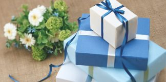 stack of presents wrapped in blue paper and bouquet of flowers