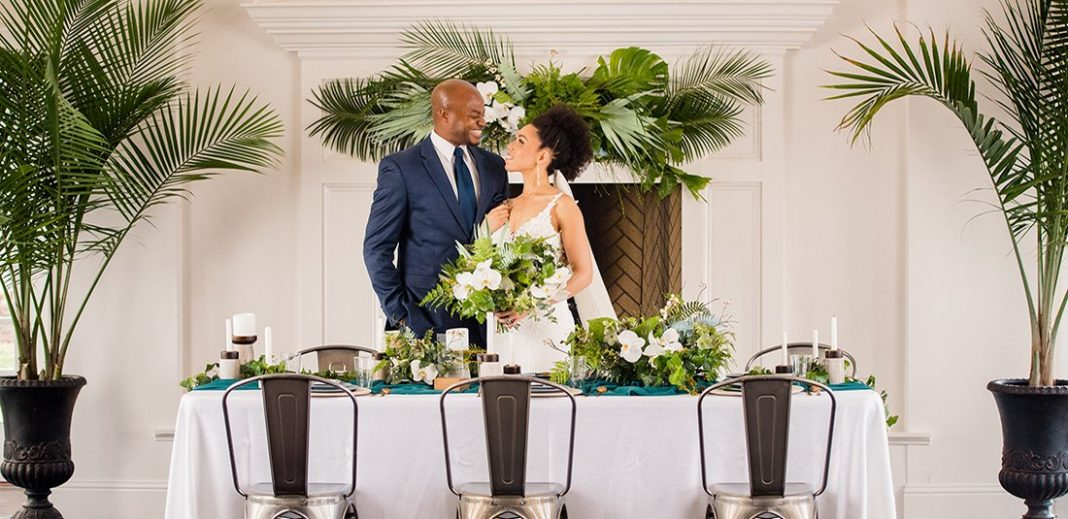 bride and groom standing at wedding reception table