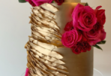 gold 3 tier wedding cake with gold ruffles and bright pink roses