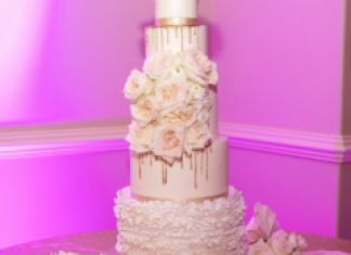 5 tier glamorous white wedding cake with ivory garden roses and gold metallic drips